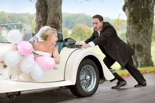 Sweden, Vastra Gotaland, Naas, Groom pushing car with brideの写真素材 [FYI02741945]