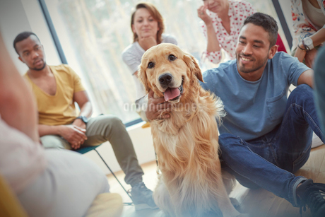 Man petting dog in group therapy sessionの写真素材 [FYI02741946]