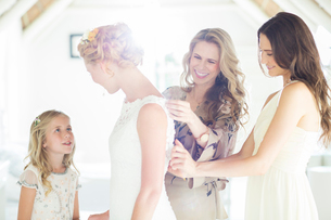 Matron of honor and bridesmaid helping bride with dressing in domestic roomの写真素材 [FYI02741954]