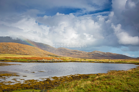 Tranquil view clouds and rainbow over rolling hills beyond lake, Loch Aineort, South Uist, Outer Hebの写真素材 [FYI02741961]
