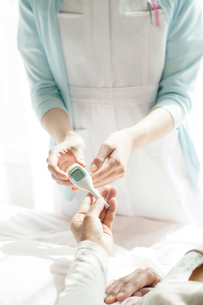 患者に体温計を渡す看護師(訪問医療)の写真素材 [FYI02742321]