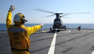 Boatswain's Mate directs a CH-46 Sea Knight helicopter aboard USの写真素材 [FYI02742643]