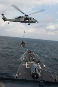 An MH-60S Sea Hawk helicopter delivers supplies to USS Mobilの写真素材 [FYI02742929]