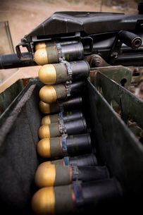 Linked 40mm rounds feed into a Mark 19 grenade launcher.の写真素材 [FYI02743045]