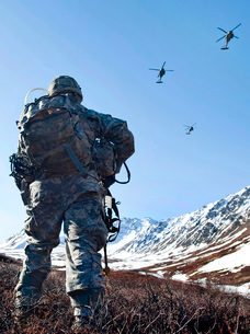 Soldier patrols through Alaska Chugach Range as UH-60 Black Hawk helicopters fly above.の写真素材 [FYI02743119]