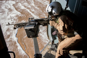 Afghan Air Force gunner fires an M-240 weapon from an Mi-17.の写真素材 [FYI02743405]