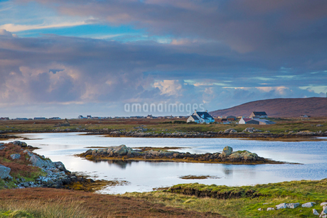 Tranquil scene clouds over lake and fishing village, Lochboisdale, South Uist, Outer Hebridesの写真素材 [FYI02744420]