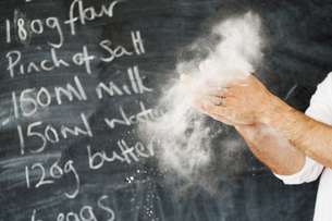 Close up of a baker standing in front of a blackboard, dusting his hands with flour.の写真素材 [FYI02750369]