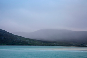 Fog rolling over tranquil mountains and ocean, Golden Road, Harris, Outer Hebridesの写真素材 [FYI02756249]