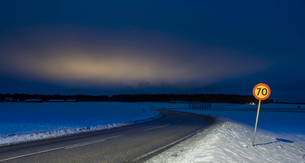 Sweden, Sodermanland, Skavsta, Speed limit sing by road in winter at duskの写真素材 [FYI02756424]