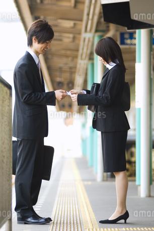 名刺交換するビジネスマンとビジネスウーマンの写真素材 [FYI02810096]