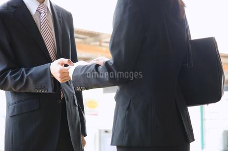 名刺交換するビジネスマンとビジネスウーマンの写真素材 [FYI02810124]