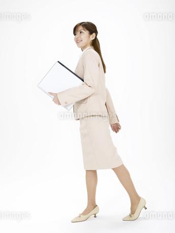 ノートパソコンを持って歩くビジネスウーマンの写真素材 [FYI02811251]