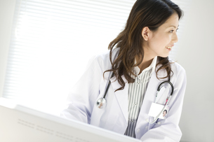 パソコンの前に座っている女医の横顔の写真素材 [FYI02811626]