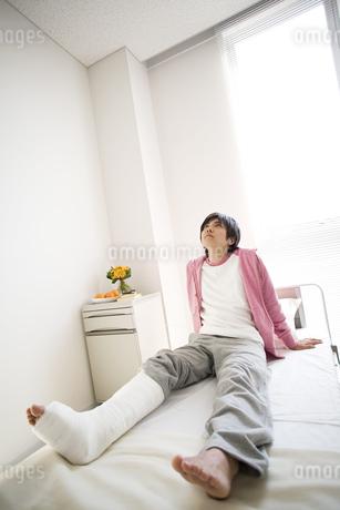 病室のベッドに座る骨折している男性の写真素材 [FYI02811634]