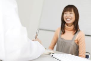女性に問診している女医の手元の写真素材 [FYI02811637]