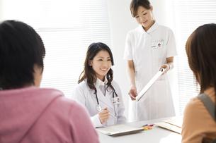 カップルと話す女医とカルテを持つ看護師の写真素材 [FYI02811639]