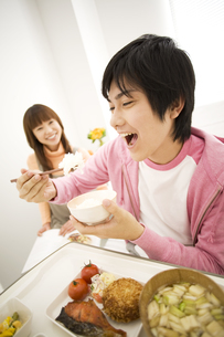 病院食を食べる彼氏と見守る彼女の写真素材 [FYI02811645]