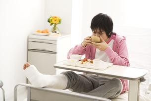 病院食を食べる骨折している男性の写真素材 [FYI02811664]
