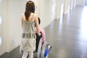 骨折した彼氏の乗る車椅子を押す彼女の写真素材 [FYI02811677]