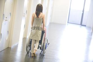 骨折した彼氏の乗る車椅子を押す彼女の写真素材 [FYI02811684]