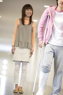 松葉杖をついて歩く彼氏と彼女の写真素材 [FYI02811690]