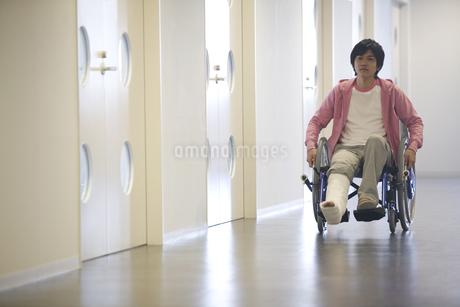 車椅子に乗っている骨折した男性の写真素材 [FYI02811692]