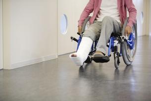 車椅子に乗っている骨折した男性の写真素材 [FYI02811695]