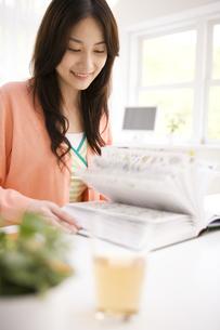 図鑑を見ている女性の写真素材 [FYI02811777]