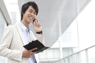スマートフォンで電話しているビジネスマンの写真素材 [FYI02811876]