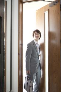 玄関扉を開けるビジネスマンの写真素材 [FYI02812027]