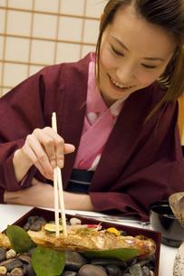 魚を食べている浴衣の女性の写真素材 [FYI02812056]
