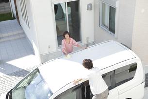 家の前で洗車をする夫婦の写真素材 [FYI02812062]
