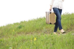 トランクを持って歩く女性の足元の写真素材 [FYI02812142]