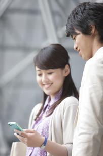 スマートフォンを見ているビジネスパーソン2人の写真素材 [FYI02812246]