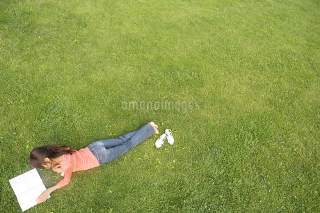草原でうつ伏せになって本を読む女性の写真素材 [FYI02812295]