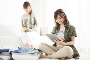 タブレットPCを操作する娘と母親の写真素材 [FYI02812342]