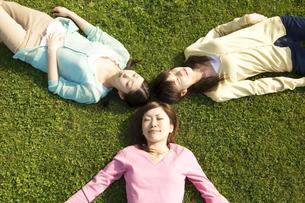 芝生に寝転ぶ3人の女性の写真素材 [FYI02812347]