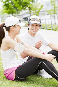 芝生に座るスポーツウェア姿のカップルの写真素材 [FYI02812359]