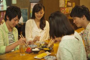 居酒屋で食事をする若者4人の写真素材 [FYI02812397]