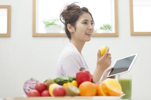 キッチンでレモンを持つ女性の写真素材 [FYI02812528]