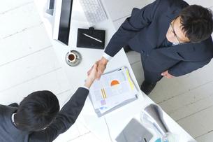 握手するビジネスマン2人とオフィスイメージの写真素材 [FYI02812642]