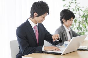 パソコンを操作するビジネス男女2人の写真素材 [FYI02812648]