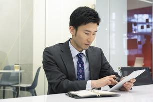 タブレットPCを操作するビジネスマンの写真素材 [FYI02812794]