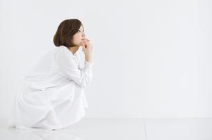 しゃがんで上を向いている女性の写真素材 [FYI02812892]