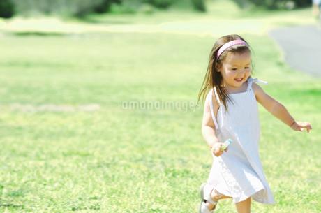 芝生を走る女の子の写真素材 [FYI02812950]