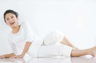 起き上がろうとする笑顔の女性の写真素材 [FYI02812953]