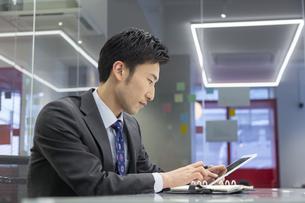タブレットPCを操作するビジネスマンの写真素材 [FYI02812967]