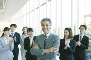 腕を組むビジネスマンと拍手をするビジネス男女の写真素材 [FYI02813005]