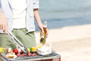 浜辺でバーベキューをする男性の写真素材 [FYI02813275]